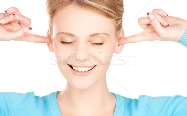 smiling woman with hands over ears Stock photo © dolgachov