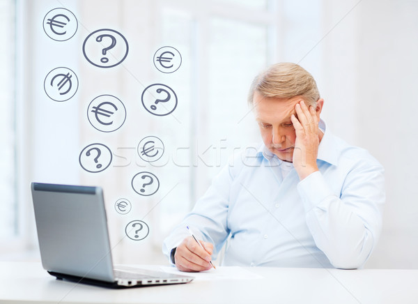 Stock photo: old man filling a form at home