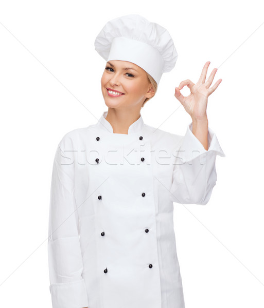 smiling female chef showing ok hand sign Stock photo © dolgachov