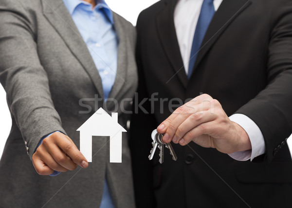 Stock photo: businessman and businesswoman holding white house