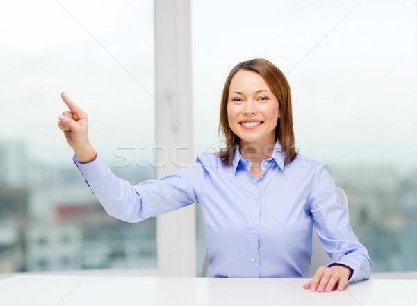 Femme souriante pointant quelque chose imaginaire affaires éducation Photo stock © dolgachov