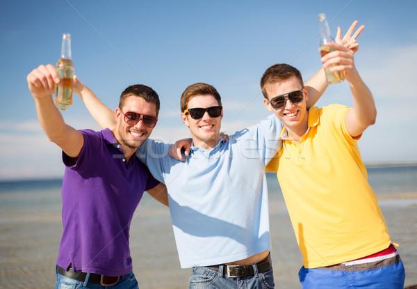 Férfi barátok tengerpart üvegek ital nyár Stock fotó © dolgachov