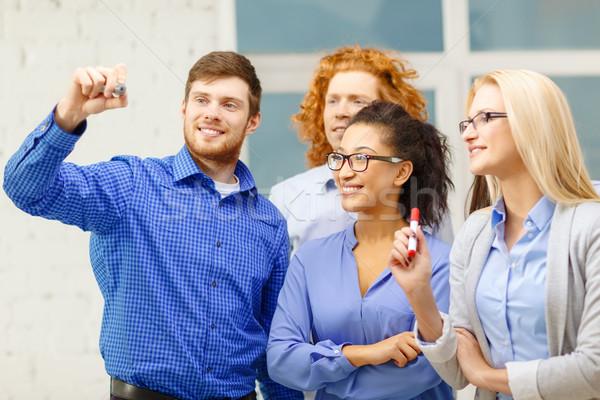 smiling creative team writing on virtual screen Stock photo © dolgachov