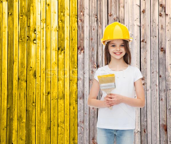 smiling little girl in helmet with paint brush Stock photo © dolgachov