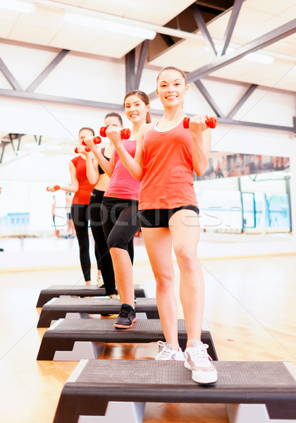 group of smiling female with dumbbells and step Stock photo © dolgachov