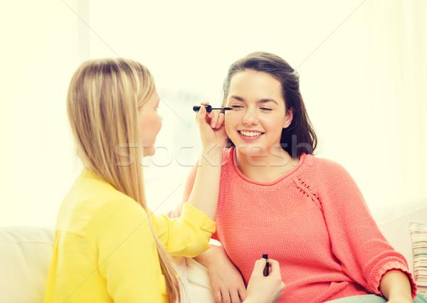 two smiling teenage girls applying make up at home Stock photo © dolgachov