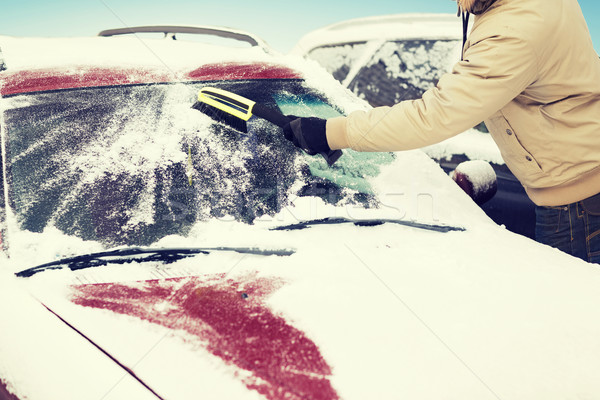 man cleaning snow from car windshield with brush Stock photo © dolgachov