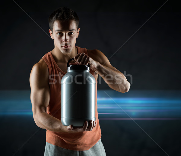 young male bodybuilder holding jar with protein Stock photo © dolgachov