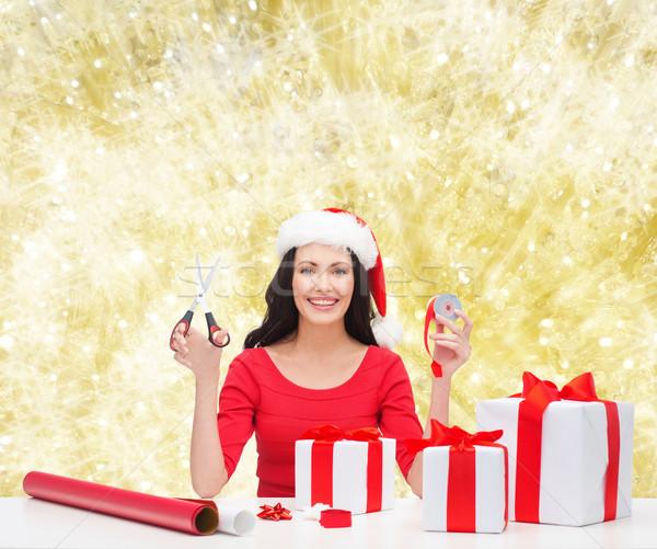 Mosolygó nő mikulás segítő kalap csomagol ajándékok Stock fotó © dolgachov