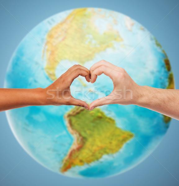 human hands showing heart shape over earth globe Stock photo © dolgachov