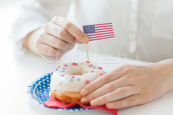 Stock photo: female hands decorating donut with american flag