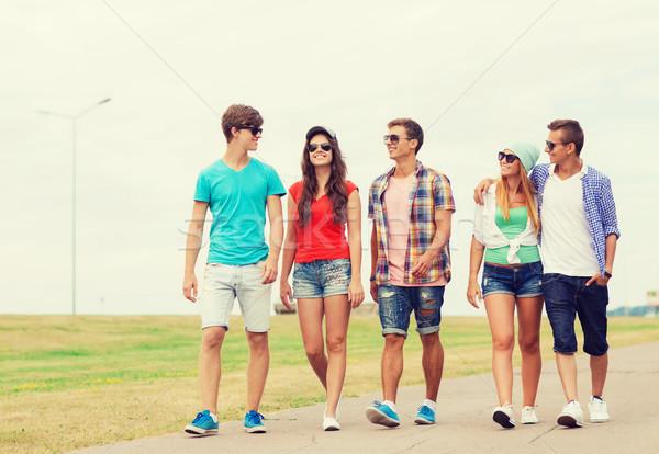 group of smiling teenagers walking outdoors Stock photo © dolgachov