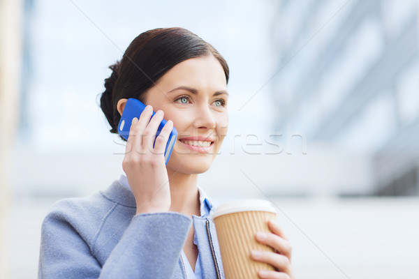 Stock photo: smiling woman with coffee calling on smartphone