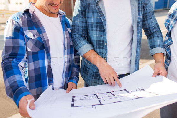 close up of smiling builders with blueprint Stock photo © dolgachov