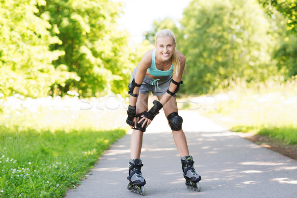 Stock photo: happy young woman in rollerskates riding outdoors