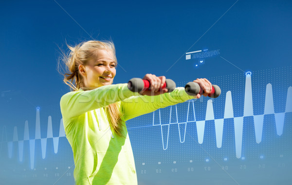 sporty woman with light dumbbells outdoors Stock photo © dolgachov