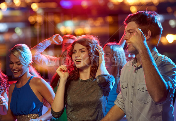 group of happy friends dancing in night club Stock photo © dolgachov