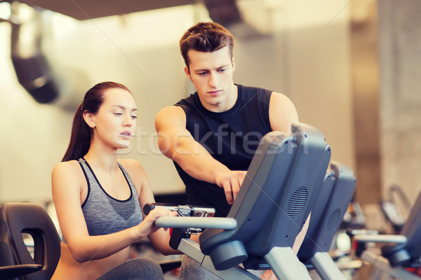 woman with trainer on exercise bike in gym Stock photo © dolgachov