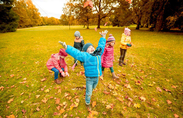 happy children playing with autumn leaves in park Stock photo © dolgachov