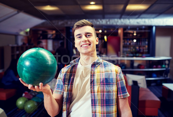 happy young man holding ball in bowling club Stock photo © dolgachov