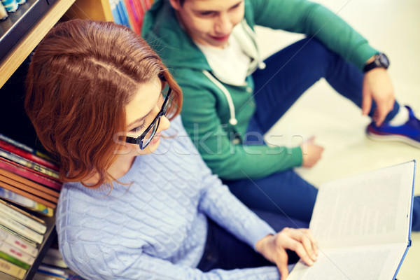 close up of happy students reading book in library Stock photo © dolgachov