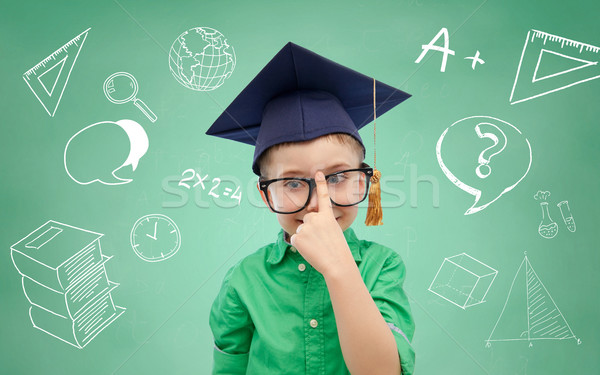 boy in bachelor hat and eyeglasses over blackboard Stock photo © dolgachov