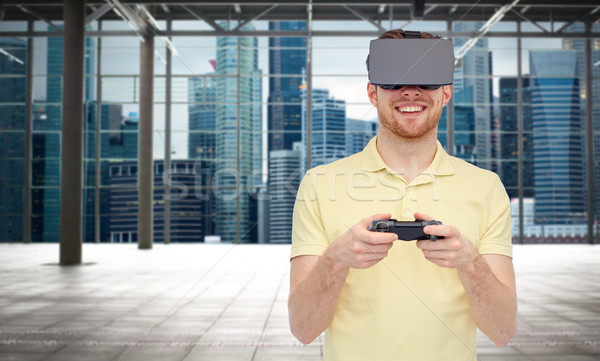 happy man in virtual reality headset with gamepad Stock photo © dolgachov