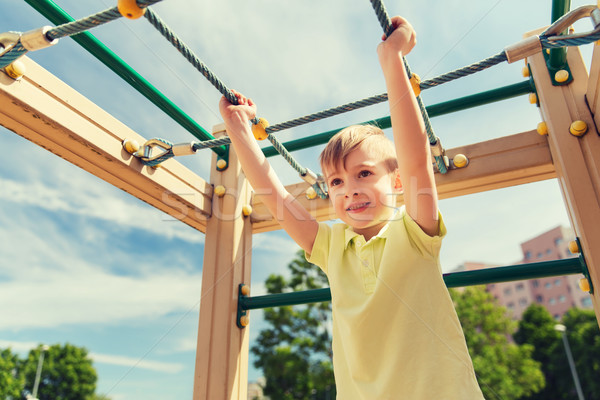 happy little boy climbing on children playground Stock photo © dolgachov