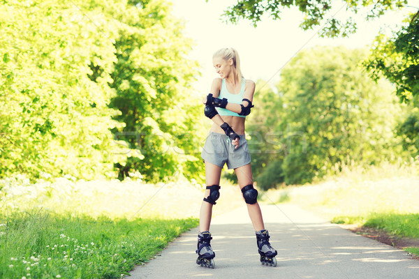 happy young woman in roller skates riding outdoors Stock photo © dolgachov