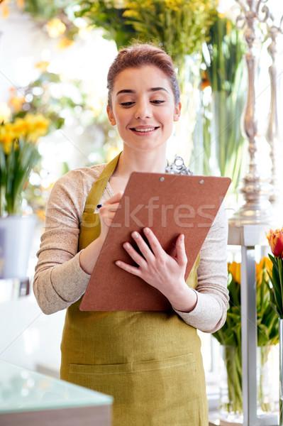 Fleuriste femme presse-papiers personnes vente Photo stock © dolgachov