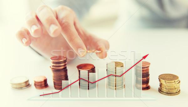 Femminile mano monete colonne business Foto d'archivio © dolgachov