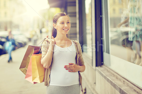 happy pregnant woman with shopping bags at city Stock photo © dolgachov