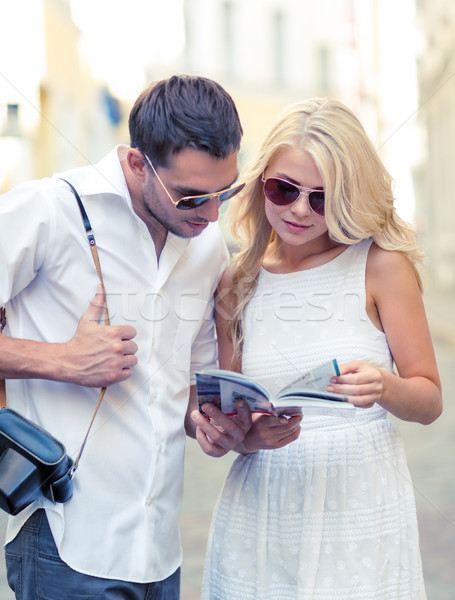 couple with map, camera and travellers guide Stock photo © dolgachov