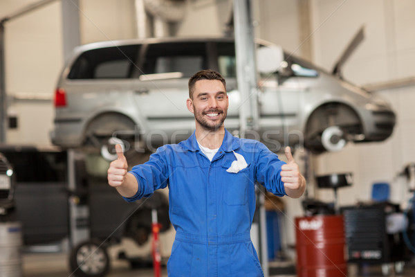 Stock photo: happy auto mechanic man or smith at car workshop