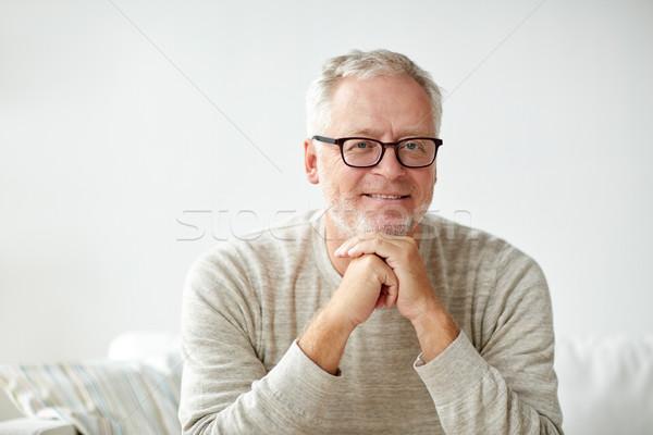 Mosolyog idős férfi szemüveg ül kanapé Stock fotó © dolgachov