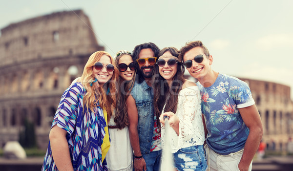 happy hippie friends with selfie stick at coliseum Stock photo © dolgachov