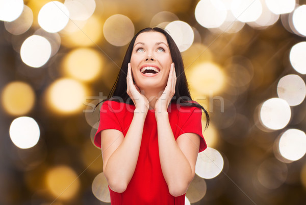 amazed laughing woman in red dress looking up Stock photo © dolgachov