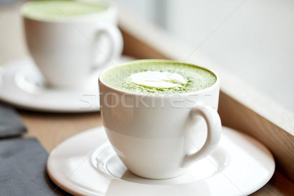 white cup of matcha green tea latte on table Stock photo © dolgachov