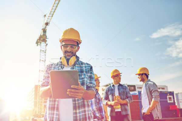 builder in hardhat with tablet pc at construction Stock photo © dolgachov