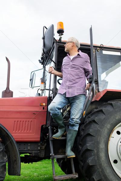 Stary rolnik na zewnątrz ciągnika gospodarstwa Zdjęcia stock © dolgachov