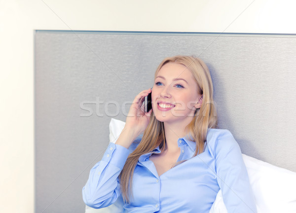 Stock photo: happy businesswoman with smartphone in hotel room