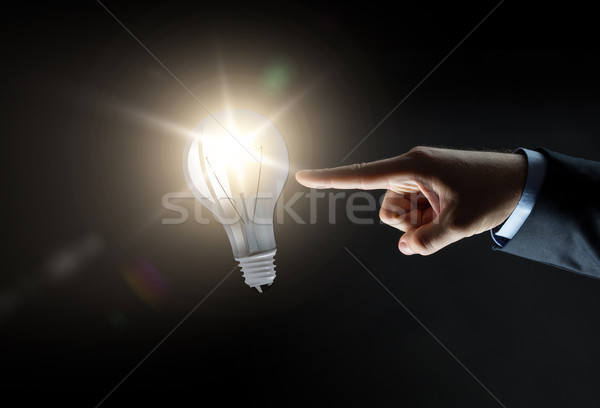 businessman pointing finger to lightbulb over dark Stock photo © dolgachov