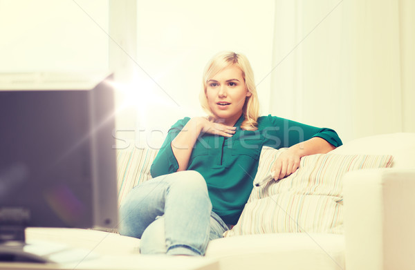 smiling woman with remote watching tv at home Stock photo © dolgachov