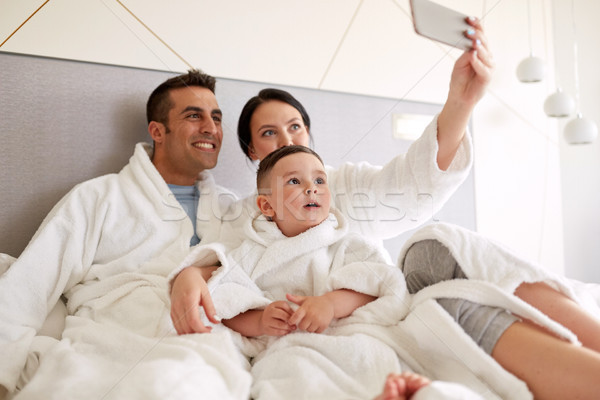 счастливая семья смартфон кровать номер в отеле люди семьи Сток-фото © dolgachov