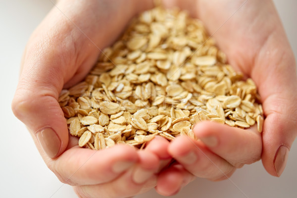 close up of hands holding oat flakes Stock photo © dolgachov