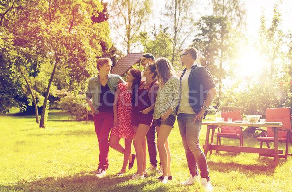 happy teenage friends talking at summer garden Stock photo © dolgachov