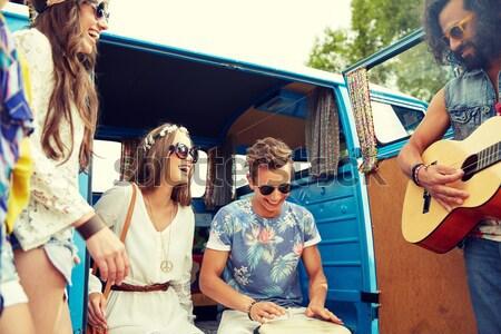 happy hippie friends playing music in minivan Stock photo © dolgachov