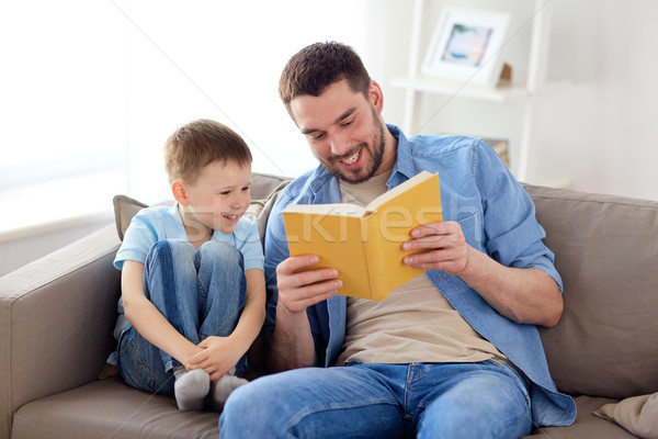 Szczęśliwy syn ojca czytania książki sofa domu Zdjęcia stock © dolgachov