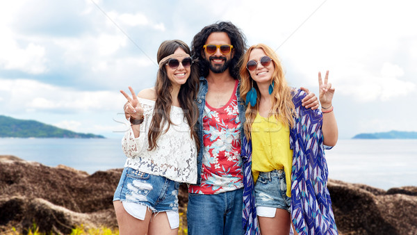 happy hippie friends showing peace on summer beach Stock photo © dolgachov