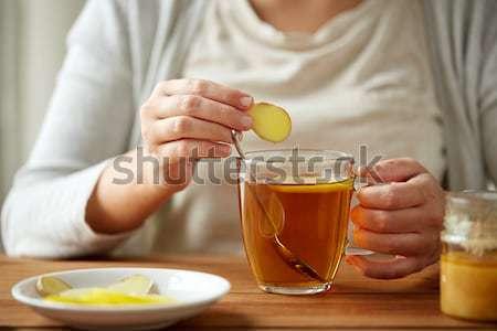 close up of woman adding lemon to tea with honey Stock photo © dolgachov